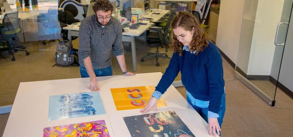 Two CCS employees look at design layouts on a table