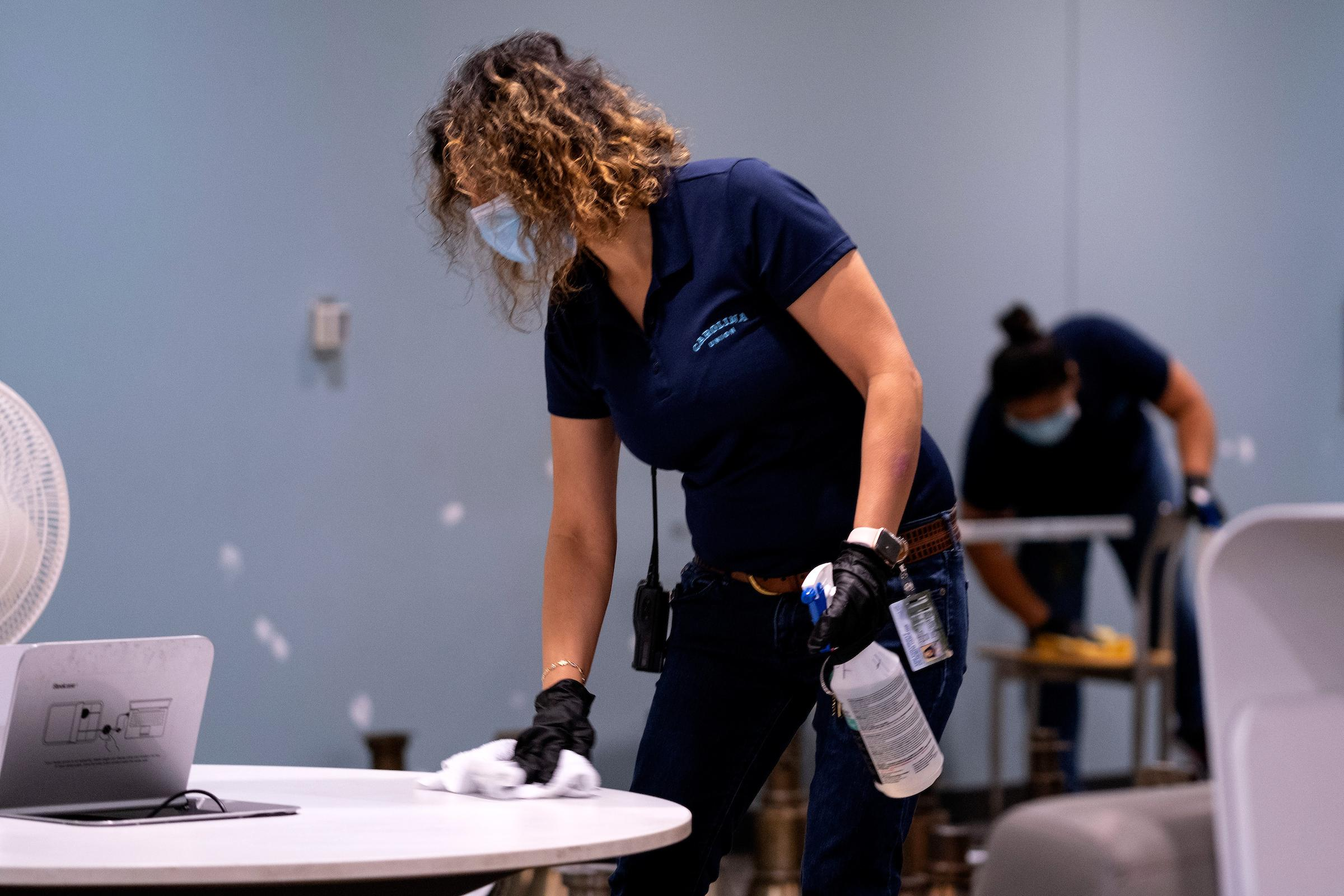 Housekeeping worker disinfecting table
