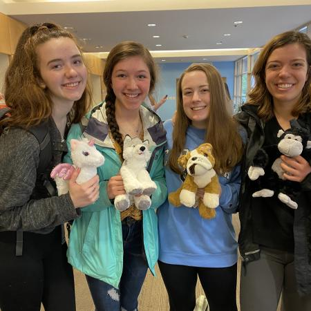 Students smiling with stuffed animals
